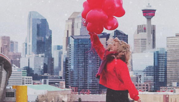 Red balloons in front of the Calgary skyline